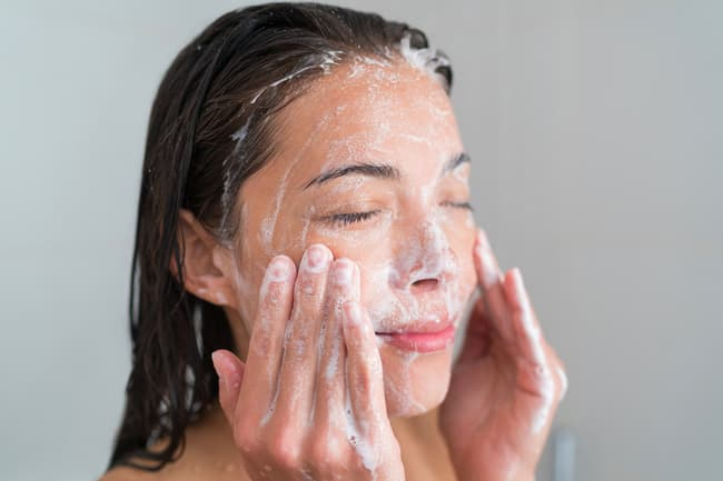 photo of woman washing her face