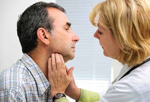 doctor examining male patients throat