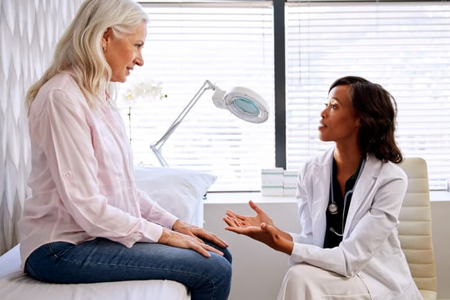 photo of doctor talking with woman