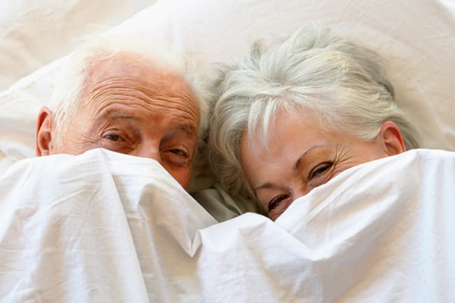 photo of mature couple under sheets