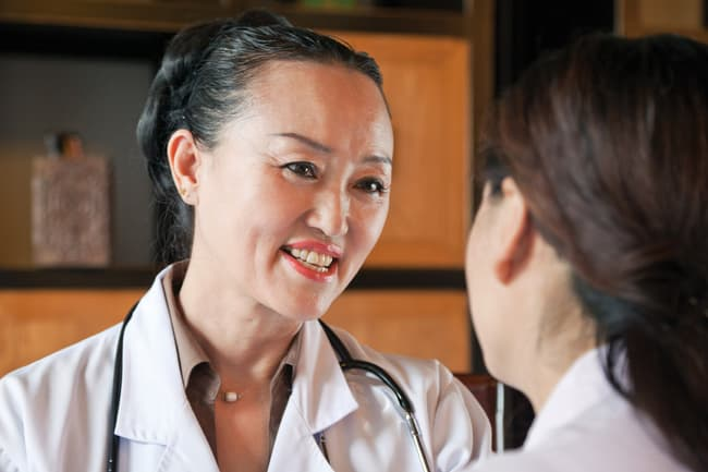 photo of female doctor talking with patient