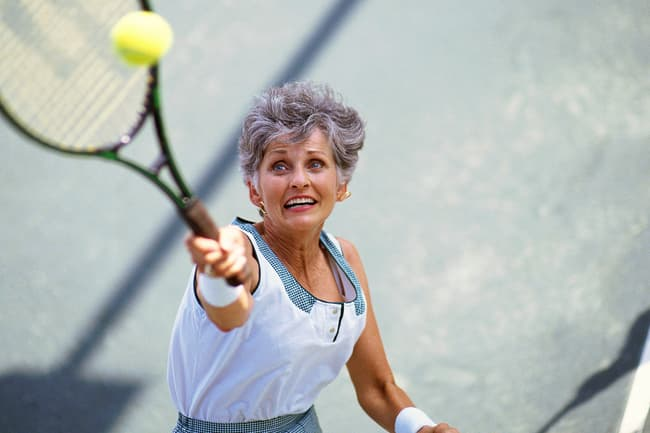 photo of mature woman playing tennis