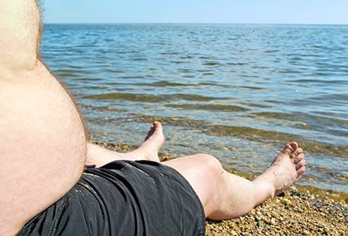 obese man sitting on shore