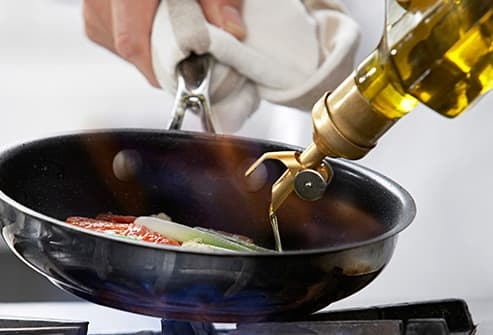 pouring olive oil into frying pan