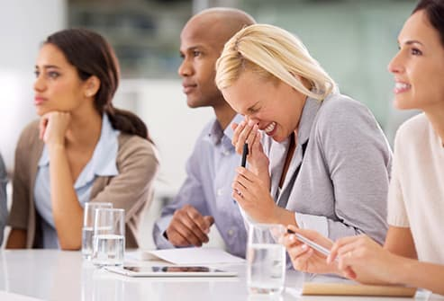 woman sneezing in meeting