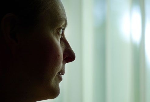 Woman silhouetted in window after chemotherapy