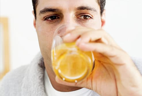Man drinking juice wearing house robe