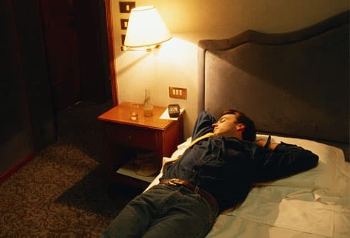 Man asleep on bed with light on, fully clothed