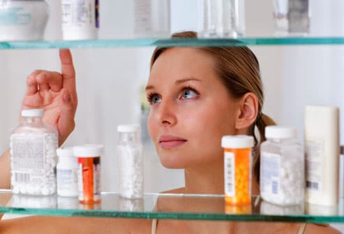 Woman selecting OTC medication from medicine chest