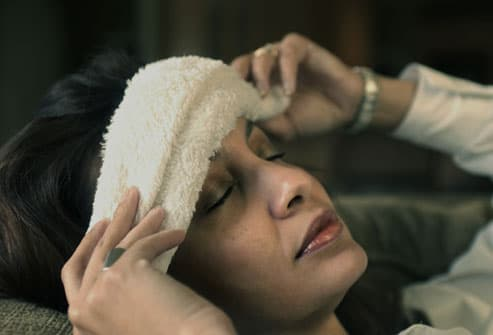 Woman with washcloth on forehead