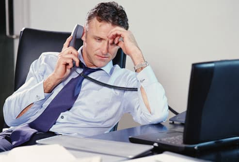 Businessman slouching on phone, head in hand