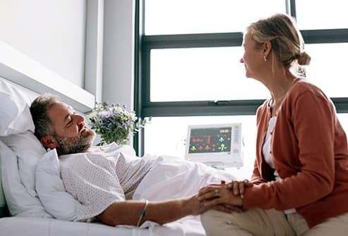 man in hospital bed holding hand