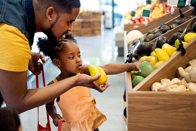 photo of father and daughter shopping for mango