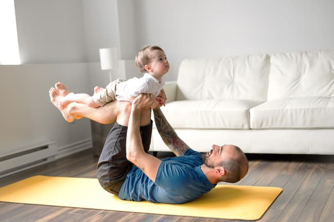 photo of father and baby doing yoga