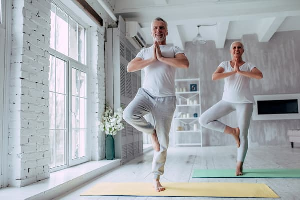 photo of mature couple doing yoga