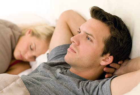 pensive man in bed with woman