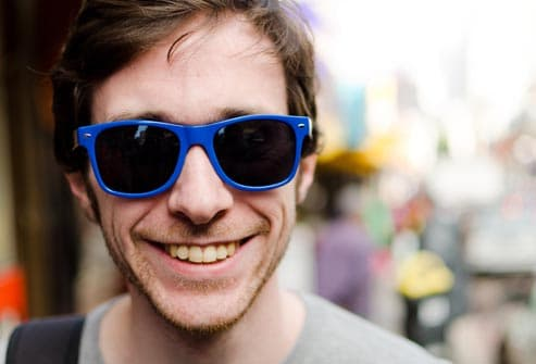 smiling man wearing blue sunglasses