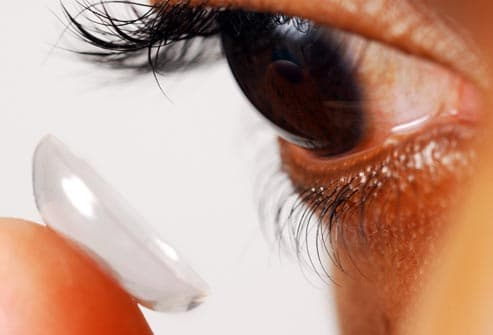 man putting contact lens onto eye