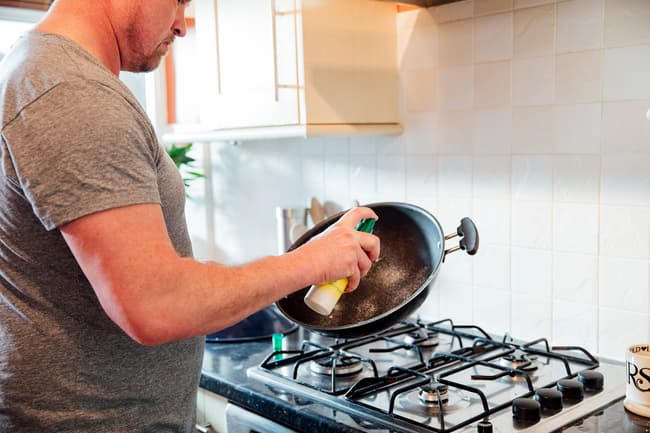 photo of man spraying frying pan