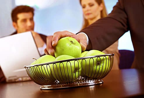 Executive reaching for apple in conference room