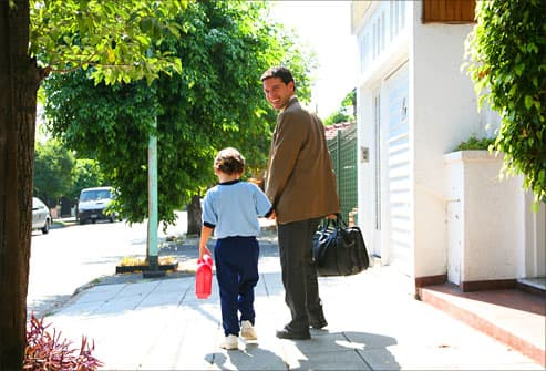 Father walking son to school on his commute