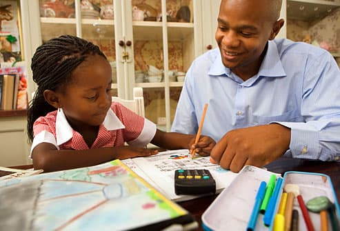 Man helping daughter with her homework