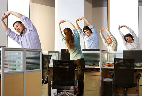 Group of office workers stretching at their desks