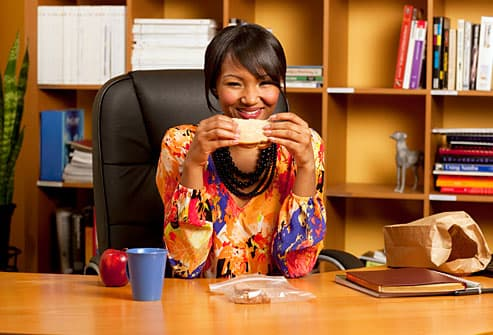 Woman eating brown bag lunch at desk