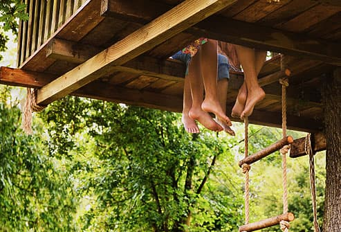 kids legs hanging from tree house