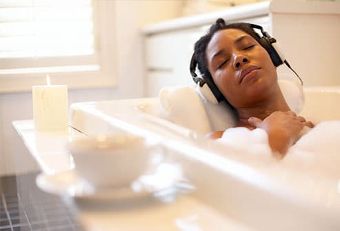Woman laying in bathtub with headphones