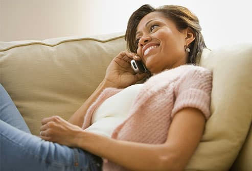 Woman reclining on  sofa talking on phone