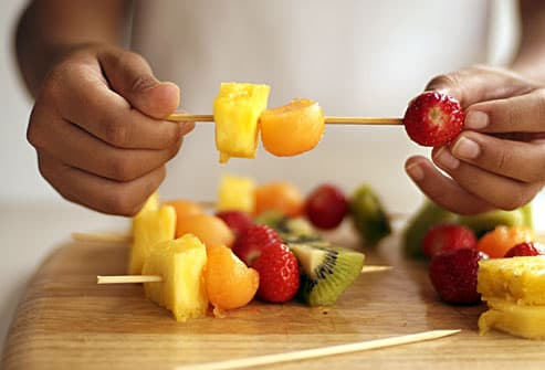 girl making fruit kabobs