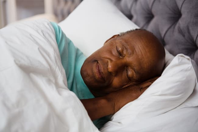 photo of man sleeping in bed