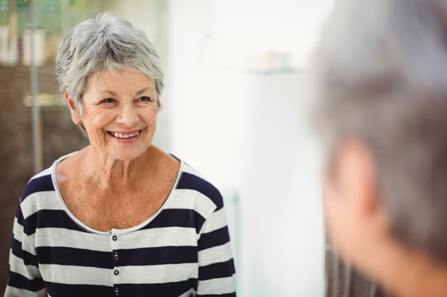 senior woman smiling at reflection in mirror