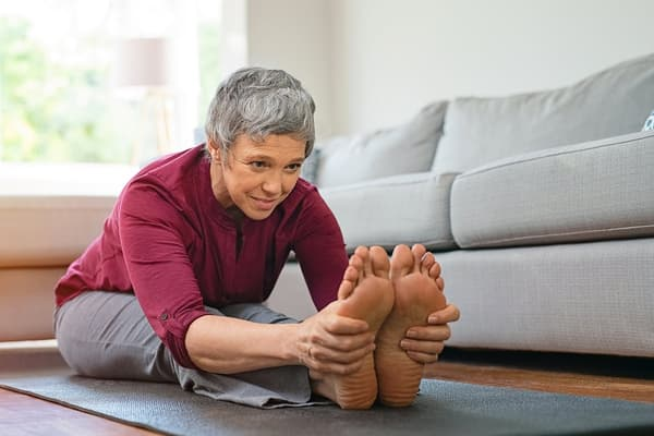 photo of mature woman stretching on exercise mat