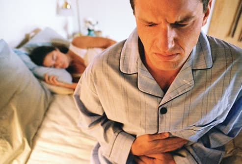 man on edge of bed with queasy stomach