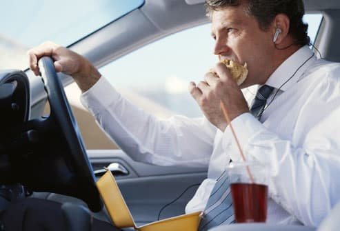 Businessman sitting in car eating fast food