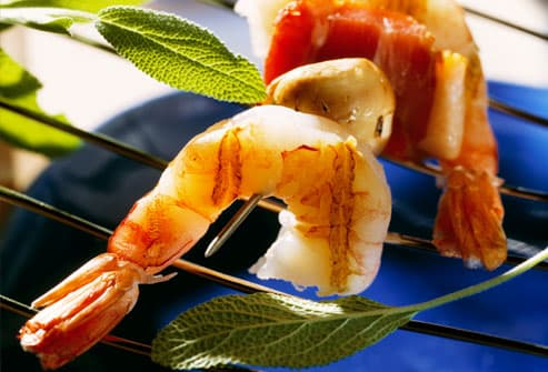 Shrimps on skewer with bacon and mushrooms