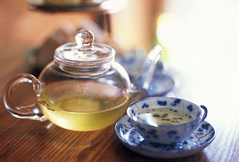 Tea pot and cup with green tea
