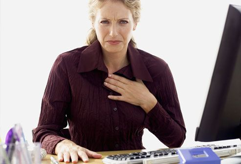 Woman at desk with hand on chest