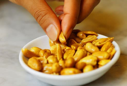 Close up of hand picking peanut from bowl
