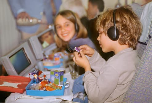 Children (6-12) on airplane having meal