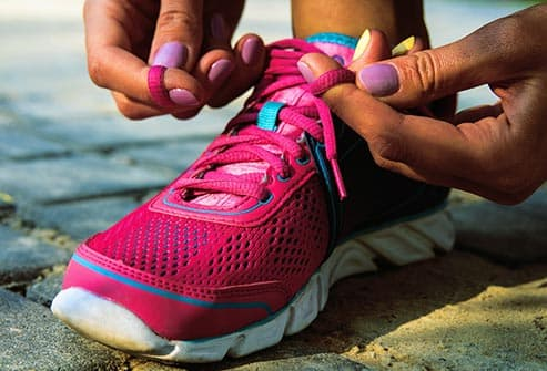 woman tying running shoe