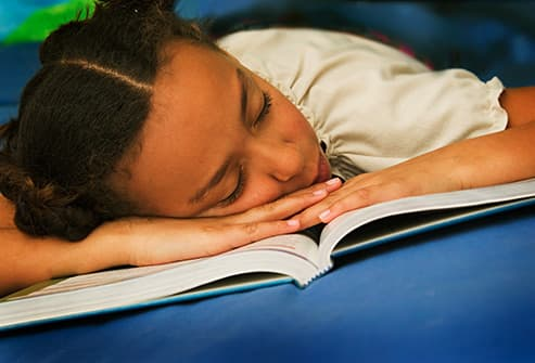 girl asleep on book
