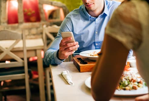 man using smartphone at dinner table