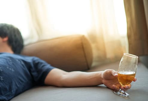 man asleep holding drink