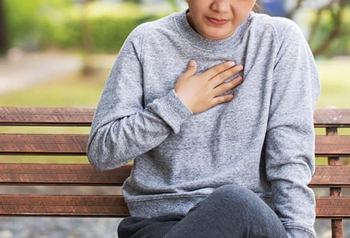 woman with heartburn on park bench