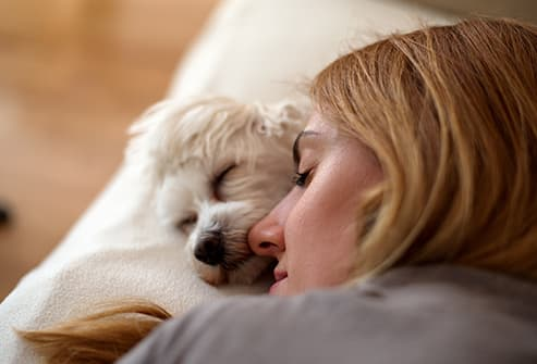 woman sleeping with dog