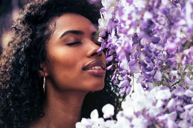 photo of woman smelling flowers