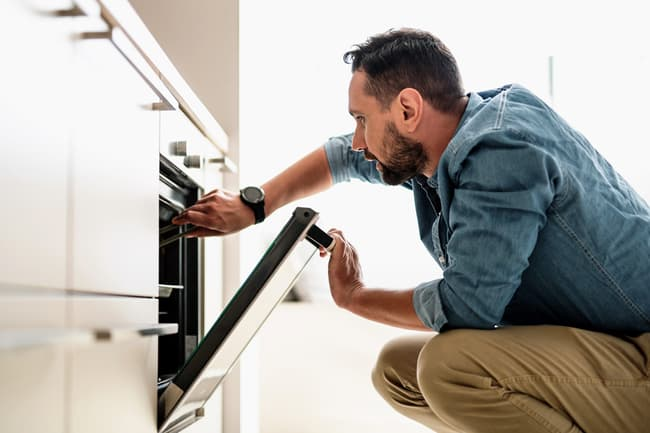 photo of man opening oven